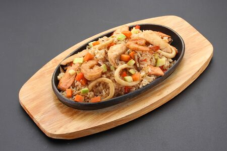 Rice with seafood. Thai cuisine. Over dark background.