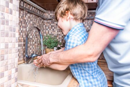 Cheerful son and his father washing hands together with soap and water in bathroom. Man and little Boy Stay safety at home and hygiene concept. Selective focus and blur people.