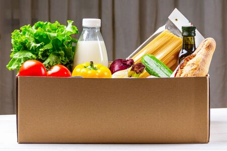 Donation box with various food. Open cardboard box with oil, vegetables, milk, canned food, cereals and pasta. Food delivery concept with space for text
