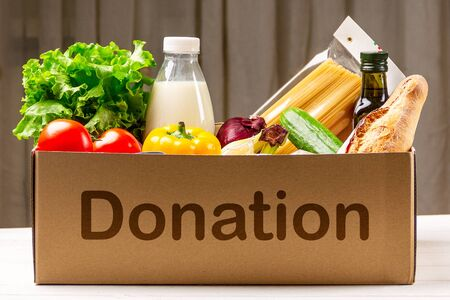 Donation box with various food. Open cardboard box with oil, vegetables, milk, canned food, cereals and pasta. Food delivery concept