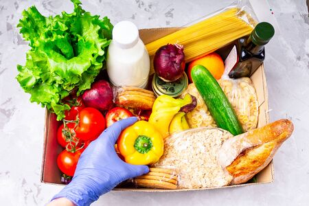 Volunteer in gloves giving food in a donation cardboard box with various food. Open cardboard box with oil, vegetables, milk, canned food, cereals and pasta. Food delivery concept .