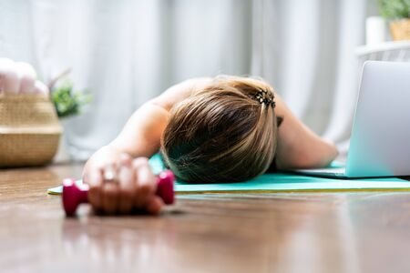 Woman falling asleep. Tired after exercise and workout. Overtraining concept. Exhausted woman lying on floor and resting after heavy cardio training in home gym at yoga mat