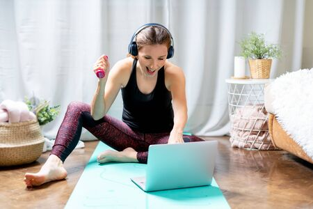 A sporty woman in sportswear and headphones working out and using laptop at home in living room, sitting on the floor with dumbbells on turquoise mat and listening music. Sport and recreation concept