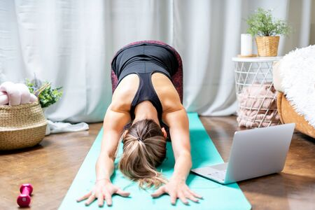 Young sporty attractive woman working out practicing yoga and using laptop and dumbbells at home in living room, doing Child exercise, Balasana . Sport and recreation concept