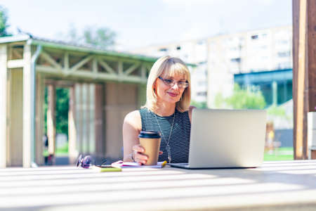 Adult Woman in glasses having video call with laptop outside in park. Happy and smiling senior working and drinking coffee. Using computer. Distance learning online education and online shops
