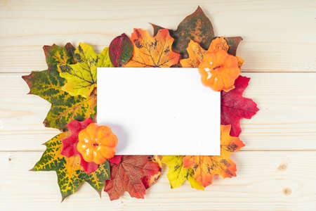 Orange pumpkins, maple leaf, berries and mock up paper blank on wooden background. Hello Fall greeting card, autumn time concept. Flat lay. Copy space.