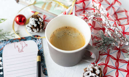 Cup of coffee, holiday decorations and paper to do list on white table top view, Christmas planning concept. Flat lay style. Happy new year.