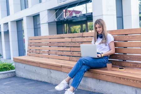 Beautiful woman with headphones working at laptop sit down on bench outside on a urban city street. Happy lady girl with wavy hair distance learning online education and shopping. Stock Photo