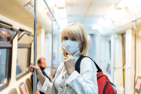 Portrait of beautiful adult woman in medical protective mask with backpack stands in the subway and looking at camera.
