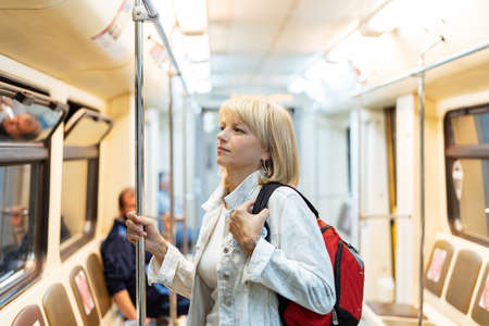 Portrait of beautiful adult woman with backpack stands in the subway and looks ahead.