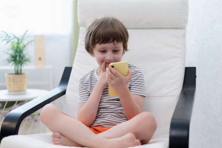 Happy little child boy playing online game, watching video on smartphone, sitting on chair entertaining in living room. Smiling small kid using funny mobile apps, enjoying free leisure time at home.