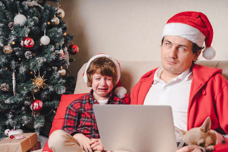 Family in Santa hat, father and crying child boy with laptop sitting on a couch in the living room with dog. Stock Photo