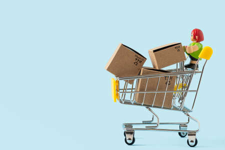 Toy shopping cart with boxes on blue background. Copy space for text or design. Sale, discount, shopping and delivery concept. Consumer society trend Reklamní fotografie
