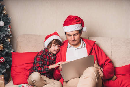 Father with child son and puppy dog in Santa hats having a video call on Christmas day at laptop, sitting on a couch in the living room with Christmas tree at home