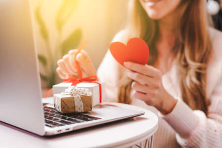 Smiling Woman with Valentine greeting card and gift box having a video call chat on laptop, online shopping, enjoy holidays at home. Selective focus 写真素材