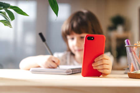 Back to school. Distance learning online education. Caucasian smile kid boy studying at home with mobile smart phone and doing school homework. Thinking child siting at table with cell phone