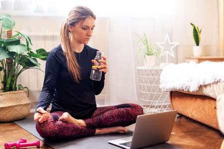 Young woman in sportswear sitting in lotus position, doing yoga exercise indoors at home, meditating with laptop and bottle of water