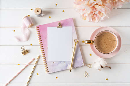 Top view of white working table background with blank paper notebook, cup of coffee. Flat lay peonies flowers, golden paper binder clips. Notepad and pen. Desktop mockup, workspace, stationery.