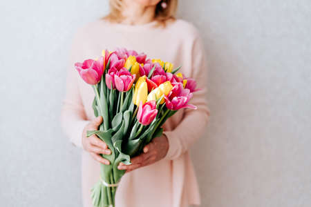Portrait of cropped woman with blonde hair hiding her face, and holding bouquet of pink and yellow tulip flowers. White background, copy space, close up.