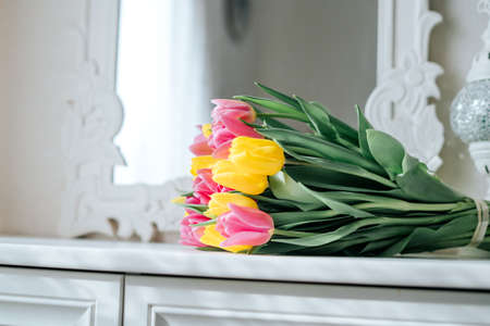 Fresh spring yellow and pink tulips bouquet on white wood table background in mirror with copy space for text. Love, easter, International Women, Mother and Happy Valentine day concept