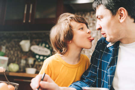 Close up of happy father and son making faces sticking his tongue out. Kid boy shows his tongue to his dad and having fun with him in the kitchen. Family with child in yellow t shirt painting at home.