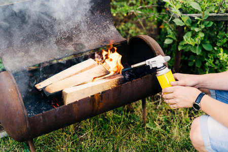 Close up man holds a gas burner with a balloon and makes a fire in the grill. Flame gun on the background of green grass in the evening in the back yard. Men hands light a fire.