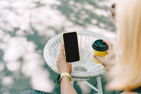 Cropped of womans hands holding yellow mobile phone with blank screen of gadget. Digital cellphone with mock up. Woman sitting cafe restaurant and drinking coffee. Copy space and mockup scene.