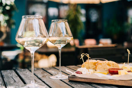 A wooden table in a restaurant with a cheese plate, grape, honey bread and white wine. Wine glasses and cheese served for a party in a blurred bar or a restaurant on terrace at a sunny summer day. Banque d'images