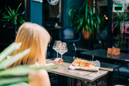Young woman sitting in cafe outdoors with glasses and blurry restaurant background scene, drinking white wine and eating cheese. Summer sunny day on patio outdoors. Banque d'images