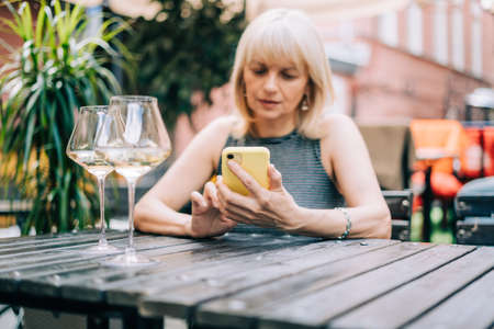 Adult mature woman texting messaging at mobile phone in bar outdoors with wine glasses and blurry restaurant, drinking white wine. People using technology cellphone. Lifestyle at summer sunny day Banque d'images
