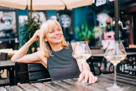 Happy smiling adult mature woman sitting in bar outdoors with wine glasses and blurry restaurant background scene, drinking white wine. Summer sunny day on patio. People lifestyle Banque d'images