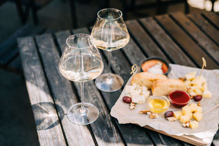 A wooden table in a restaurant with a cheese plate, grape, honey bread and white wine. Wine glasses and cheese served for a party in a bar or a restaurant on terrace at a sunny day. Banque d'images