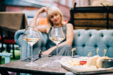 Happy adult woman sitting on couch in bar outdoors with wine glasses and blurry restaurant background scene, drinking white wine and eating cheese. Summer sunny day on patio. People lifestyle Banque d'images
