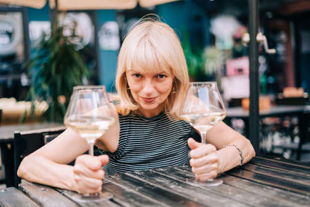 Happy funny adult mature woman sitting in bar outdoors and holding wine glasses in blurry restaurant background scene, drinking white wine. Summer sunny day on patio. People lifestyle