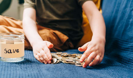 Close up of Little child kid boy hands grabbing and putting stack coins in to glass jar with save label. Donation, saving money, charity, family finance plan concept. Banque d'images