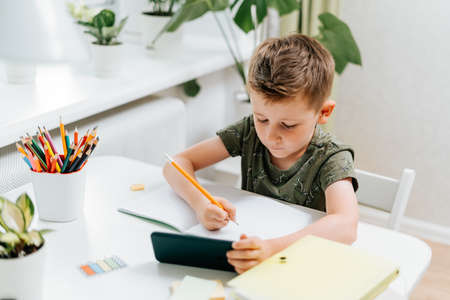Back to school. Distance learning online education. Caucasian smile kid boy studying at home with mobile smart phone and doing school homework. Thinking child with cellphone, pencil and training books