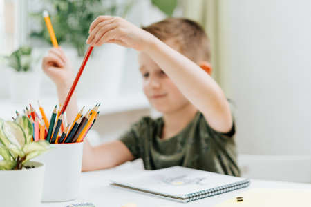 Distance learning online education. Caucasian smile kid boy studying at home with book, draw in notepad and doing school homework. Thinking child siting at table with notebook. Back to school.