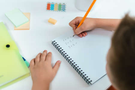 Distance learning online education. Kid boy studying at home with book, writing in notepad and doing school homework. Child siting at table with notepad. solve math problems. Back to school.