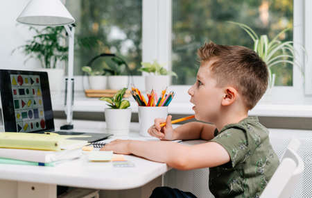 Distance learning online education. Caucasian smile kid boy studying at home with laptop and doing school homework. Surprised child siting with notebook, pencils and training books. Back to school. Banque d'images