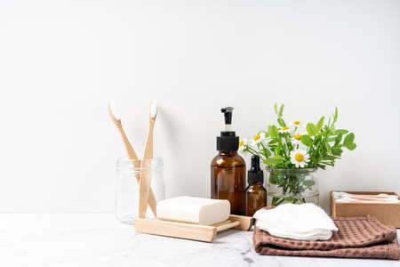 Natural bathroom and home spa tools on white background. Zero waste sustainable lifestyle concept. Bamboo toothbrush, natural soap bar, cotton pads, homemade DIY beauty products in reusable bottles.