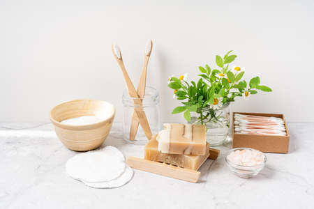 Natural bathroom and home spa tools. Zero waste sustainable lifestyle concept. Bamboo toothbrush, natural soap bar, cotton pads and swabs, flowers and brush on white background. Front view, copy space