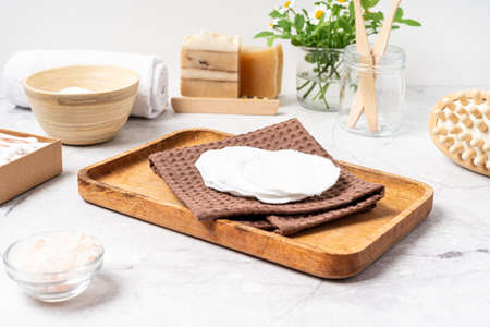 Natural bathroom and home spa tools. Zero waste sustainable lifestyle concept. Bamboo toothbrush, natural soap bar, cotton pads, homemade DIY beauty products in reusable bottles on white background.