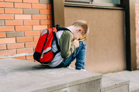 Back to school. Cute child with backpack, holding notepad and training books. School boy pupil with bag. Elementary school student going to classes. Tired Kid sitting on stairs outdoors at brick wall. Banque d'images