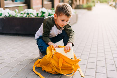 Back to school. Cute child packing backpack, holding notepad and training books going to school. Boy pupil with bag. Elementary school student going to classes. Kid walking outdoor on the city street.