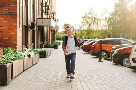 Back to school. Cute child with backpack going to school. Boy pupil with bag. Elementary school student going to classes. Kid walking outdoors on the city street after class. Banque d'images
