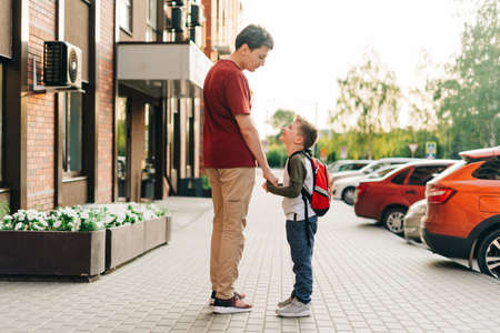 Happy father and kid son going to classes. Parent take child boy to school in first grade. Pupil of primary school go study with backpack outdoors in city street. Beginning of lessons. Back to school.
