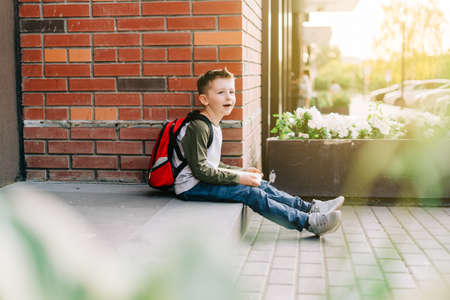 Back to school. Cute child with backpack, holding notepad and training books. School boy pupil with bag. Elementary school student going to classes. Kid sitting on stairs outdoors at brick wall. Banque d'images