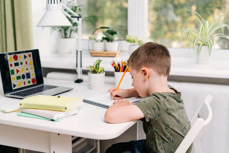 Distance learning online education. Caucasian smile kid boy studying at home with laptop and doing school homework. Thinking child siting with notebook, pencils and training books. Back to school. Banque d'images