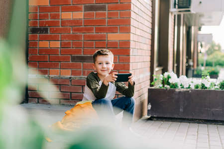 Back to school. Cute child with backpack, holding mobile phone, playing with cellphone. School boy pupil with bag. Elementary school student after classes. Kid sitting on stairs outdoors in the street