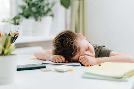 Distance learning online education. Caucasian kid boy study at home, tired asleep, resting his head on notepad, exhausting homework. Child siting with notebook and training book. Back to school.
